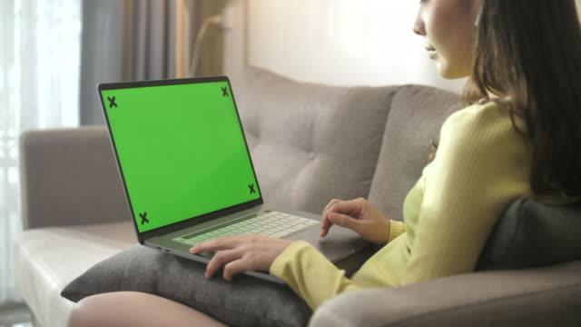 vídeos de stock e filmes b-roll de asian woman sitting on sofa using laptop with green screen at home - segurar