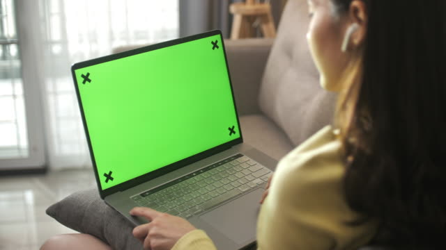 asian woman sitting on sofa using laptop with green screen at home - computer monitor stock videos & royalty-free footage