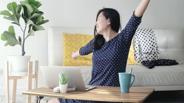 vídeos y material grabado en eventos de stock de mujer asiática sentada en el suelo y usando un portátil que trabaja desde casa durante covid-19, quédese en casa. la mujer se masajea después del trabajo. - espacio de trabajo virtual compartido