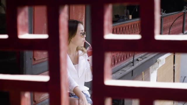 asian woman sitting on the stairs and eating strawberry smoothie - strawberry milkshake stock videos & royalty-free footage