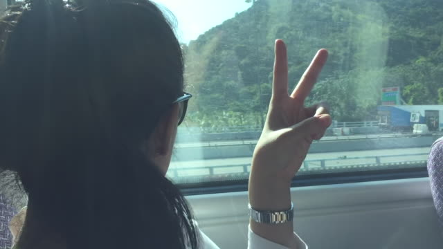 asian woman sitting on train in hong kong - escapism stock videos & royalty-free footage