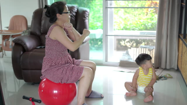 asian woman sitting on yoga ball and exercise with her son in the living room at home - exercise room stock videos & royalty-free footage