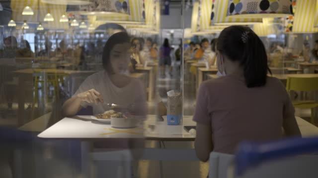 vídeos de stock, filmes e b-roll de mulher asiática sentada separada em restaurante comendo comida com partição plástica de escudo de mesa para proteger a infecção do coronavírus covid-19 - distante