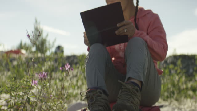 asian woman sketching in mountain meadow on vacation in a beautiful landscape - equipment点の映像素材/bロール