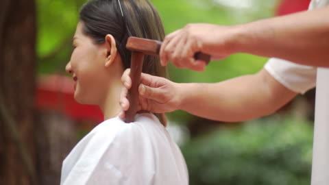 vídeos y material grabado en eventos de stock de mujer asiática sonriendo y disfrutando con masaje de martillo tradicional tailandés por masajista profesional. - balneario spa