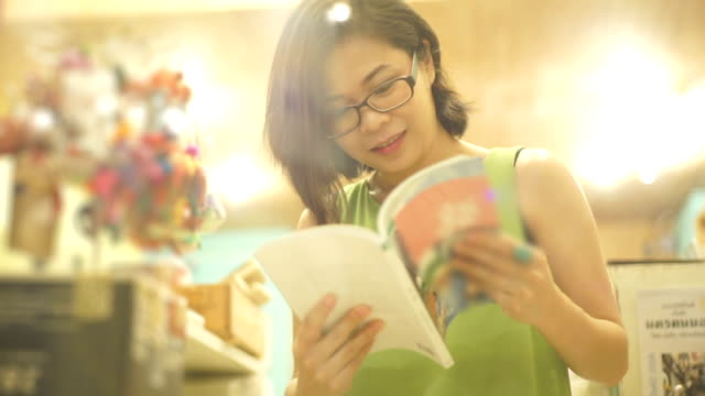 asian woman smiling while reading a book at the bookshop against shelves backgrounds. - bookseller stock videos and b-roll footage