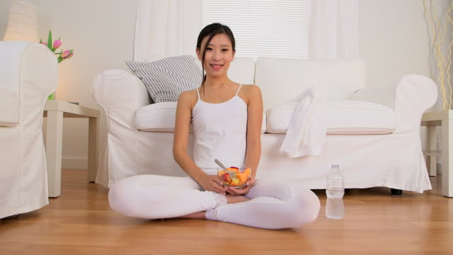 Asian woman smiling with fruit bowl