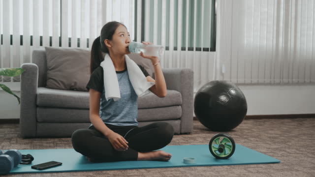asian woman sportswoman drinking from water bottle in her room after yoga exercise at home. - exercise room stock videos & royalty-free footage