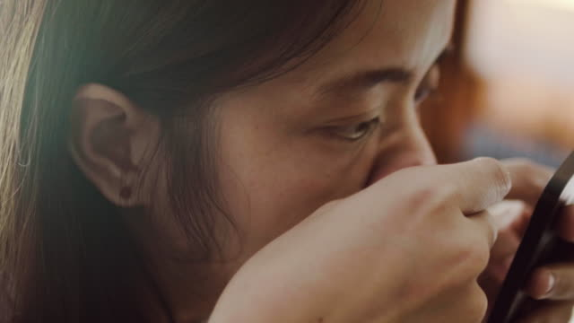 Asian woman squeezing pimples on her nose.
