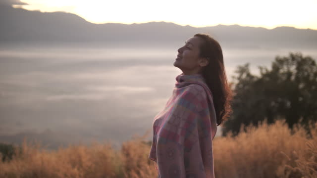 asian woman standing on top of mountain, enjoying breathtaking view at sunset - hope concept stock videos & royalty-free footage