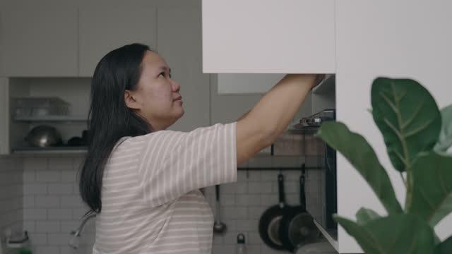vídeos y material grabado en eventos de stock de mujer asiática que se levanta para abrir el gabinete de la cocina para obtener un tazón de ingredientes - en lo alto posición descriptiva