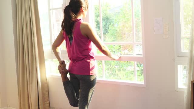 donna asiatica stressante prima di allenarsi a casa - fare lo stretching video stock e b–roll