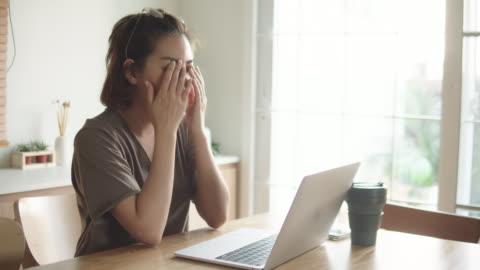 stockvideo's en b-roll-footage met aziatische vrouw die met het gebruiken van laptop thuis worstelt. - study