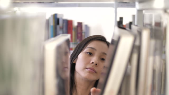 asian woman student finding and searching book in library of a university. education concept - bookshelf stock videos & royalty-free footage