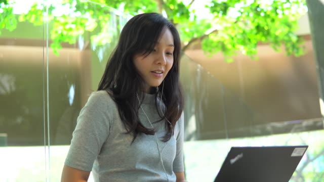 vídeos de stock, filmes e b-roll de estudante asiática na biblioteca - portable information device