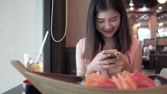 asian woman student using smartphone for chatting and sitting at table with sashimi japanese food in restaurant. - japanese food stock videos & royalty-free footage