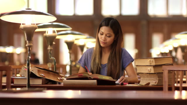 DS Asian woman studying in library's reading room
