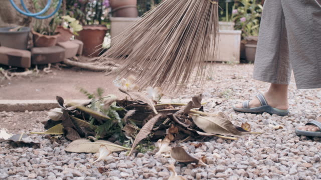vídeos y material grabado en eventos de stock de mujer asiática barriendo hojas secas en el patio trasero casa del jardín con broom.4k cámara lenta. - barrer