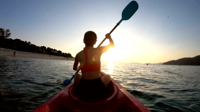 asian woman swims in the kayak in the sunset at lipe, satun, thailand - canoeing stock videos and b-roll footage