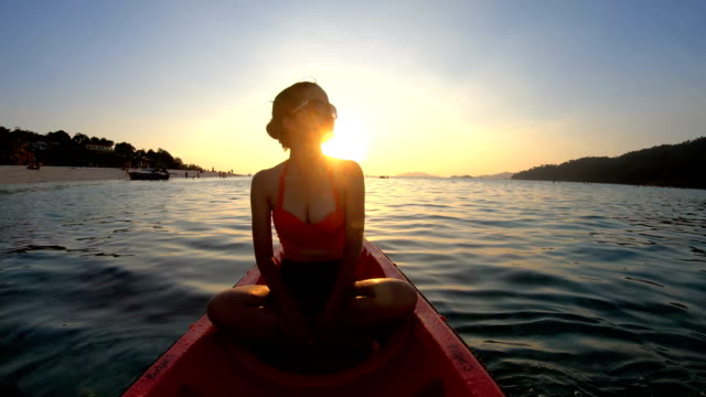 Asian woman swims in the kayak in the sunset at lipe, Satun, Thailand