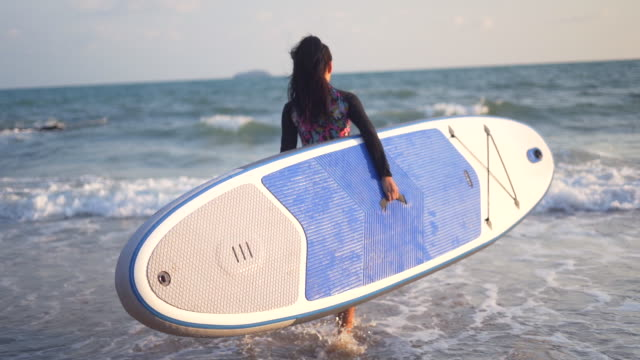 asian woman swimsuit play surfboard on the beach ,young girls in bikinis with surfboards at a beach - healthy lifestyle stock videos & royalty-free footage