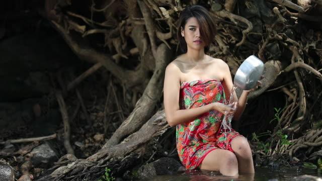 Asian woman take a bath in waterfall ,thailand