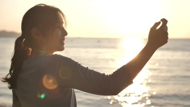 アジアの女性は写真のビーチを取ります - 人の背中点の映像素材/bロール