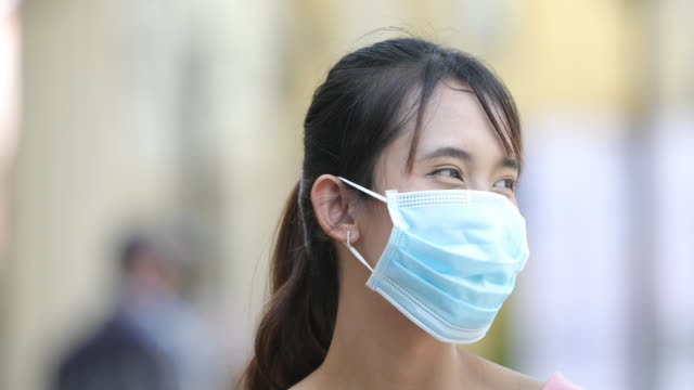 asian woman takes off a surgical face mask and smiles. - surgical mask stock videos & royalty-free footage