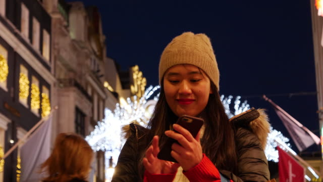 vídeos y material grabado en eventos de stock de asian woman takes photo of christmas lights and posts results on social media. - accesorio de cabeza