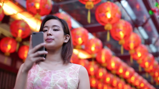 MS Asian woman taking a photo in front of red lanterns.