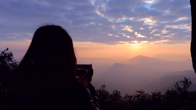 asian woman taking a photo of mountain view with foggy by smartphone , concept woman solo travel - gara sportiva individuale video stock e b–roll