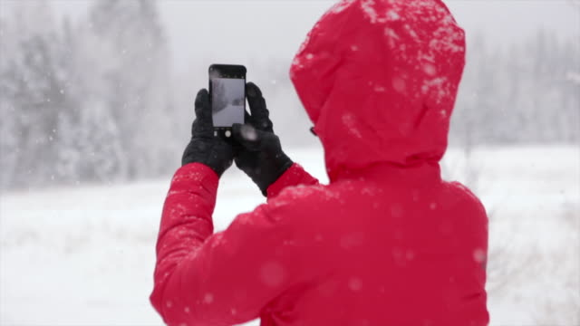 asian woman taking a selfie in a snowy park - photo messaging stock videos & royalty-free footage