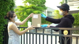 Asian woman taking package from delivery man wearing face mask and glove for protecting coronavirus covid-19