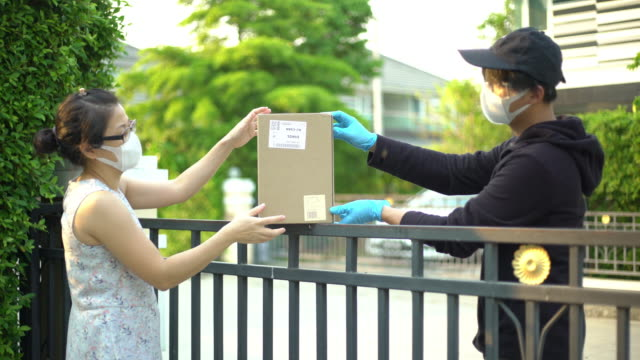 vídeos de stock e filmes b-roll de asian woman taking package from delivery man wearing face mask and glove for protecting coronavirus covid-19 - serviços essenciais
