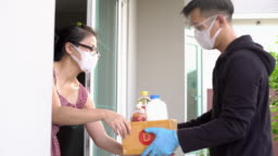 Asian woman taking package from delivery man wearing face mask and glove for protecting coronavirus covid-19 at home