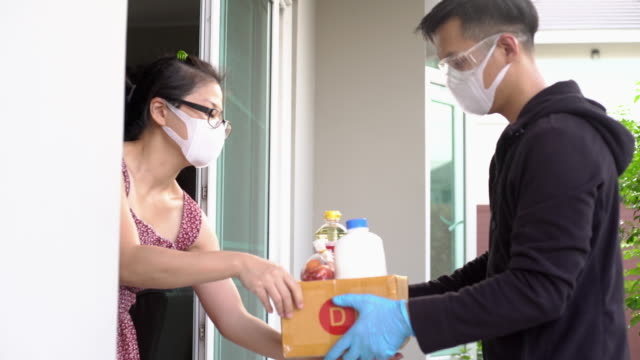 asian woman taking package from delivery man wearing face mask and glove for protecting coronavirus covid-19 at home - prevenzione delle malattie video stock e b–roll