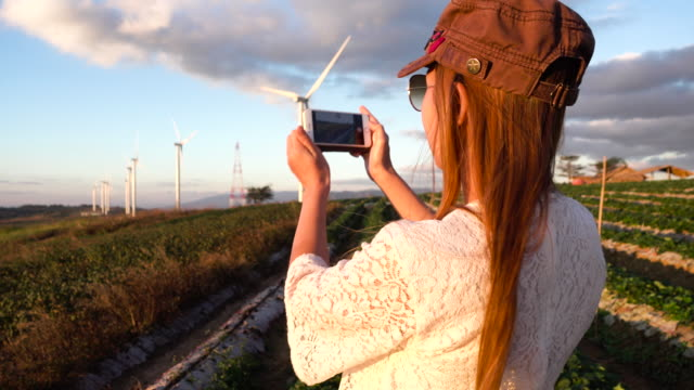Asian Woman Taking Pictures Of The Wind Turbine Farm With Smartphone