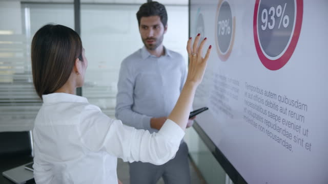 Asian woman talking about the presentation diagrams shown on the screen in meeting room with her male colleague