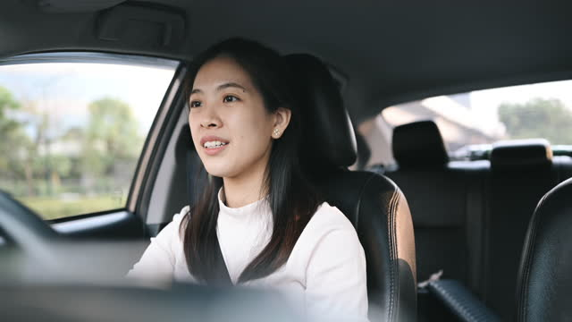 asian woman talking by wireless earphone feeling bored during driving car in bangkok thailand going to working in morning - car interior stock videos & royalty-free footage