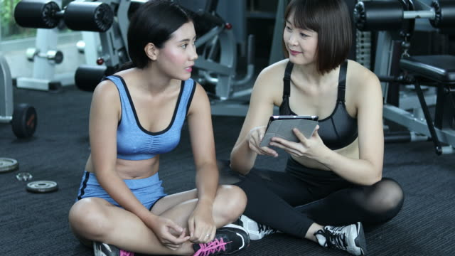 2 asian woman talking in gym with tablet