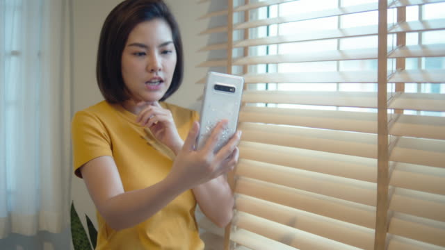 asian woman talking on video call with her smart phone at home. - remote location phone stock videos & royalty-free footage
