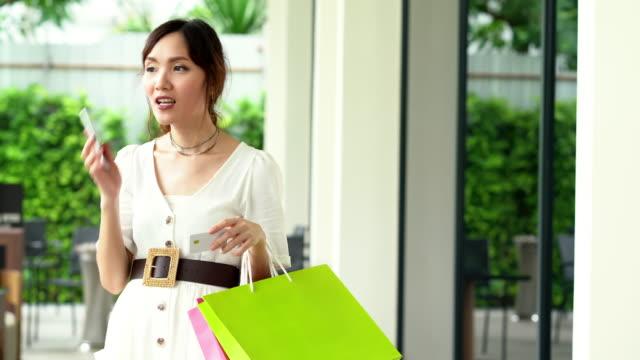 Asiatische Frau sprechendes Telefon für Treffen Freund gehen zusammen einkaufen. Addict-Shopping-Konzept.