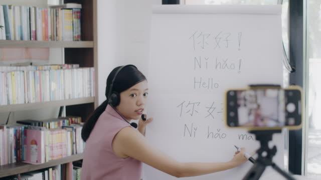 オンライン技術装置を使用して自宅のオフィスでリモートで教えているアジアの女性教師。ホームスクールで学ぶ学生に中国語を教える。自宅で働くという新しい通常のライフスタイルの概� - 言語点の映像素材/bロール