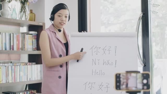asiatiska kvinna lärare undervisning på distans hemmakontor med online-teknik enhet. undervisning kinesiska språket för studenter som studerar i hemmet skolan. nytt normalt livsstilskoncept att arbeta hemifrån. - endast en tonårsflicka bildbanksvideor och videomaterial från bakom kulisserna
