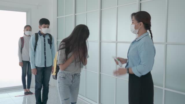 学校に戻ってくる学生、新しい正常と教育の概念ながら、covid-19の広がりに対する発熱のための温度計の温度スクリーニング学生を使用してアジアの女性教師。 - 新学期点の映像素材/bロール