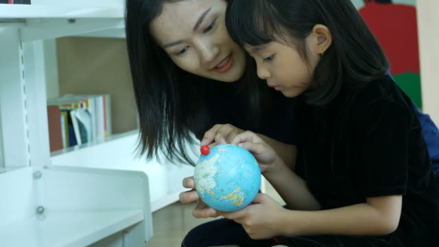 Asian woman teaching girl about geography