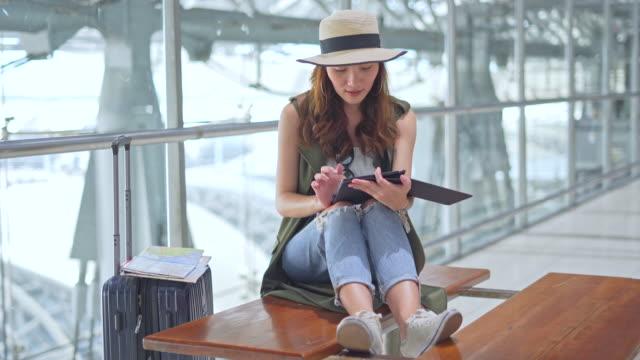 asiatische frau teenager mit tablet-findung informationen am flughafen-terminal - rucksack für reisen im urlaub sommer, junge attraktive asiatische frau passagier - bahnreisender stock-videos und b-roll-filmmaterial