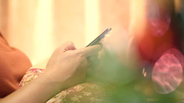 クリスマス ツリーに近いスマート フォンとアジアの女性のテキスト メッセージ