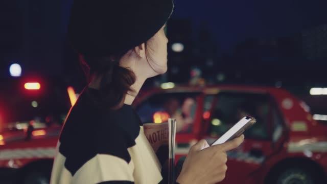 アジアの女性は夜に都会の通りにスマートフォンでテキストメッセージ。 - アジア大陸点の映像素材/bロール