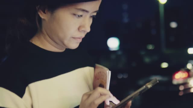 Asian woman texting with smart phone on urban street at night.